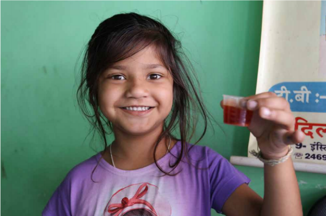 Girl holding dissolved child-friendly treatment in small cup. Image attributed from TB Alliance (2017)