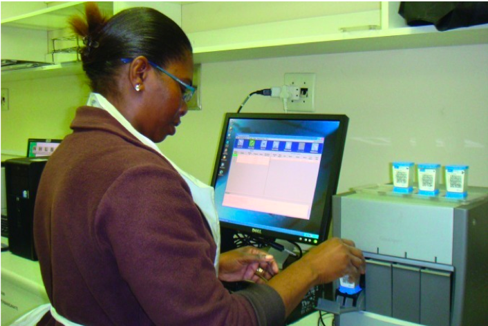 Technician in South Africa inserts cartridge containing a specimen into the Xpert machine for testing